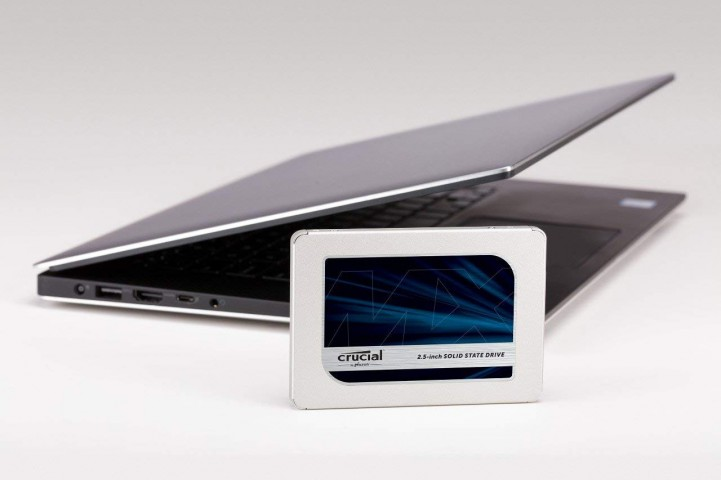 Picture of the Crucial MX500 SSD in front of a laptop.